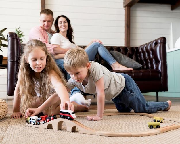 Disparo completo de padres mirando a los niños jugar
