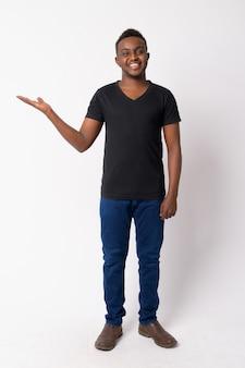 Disparo de cuerpo completo de feliz joven africano mostrando algo
