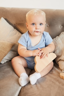 Disparo de cuerpo completo de niño con cabello rubio y ojos azules sentado en un sofá con juguete de madera