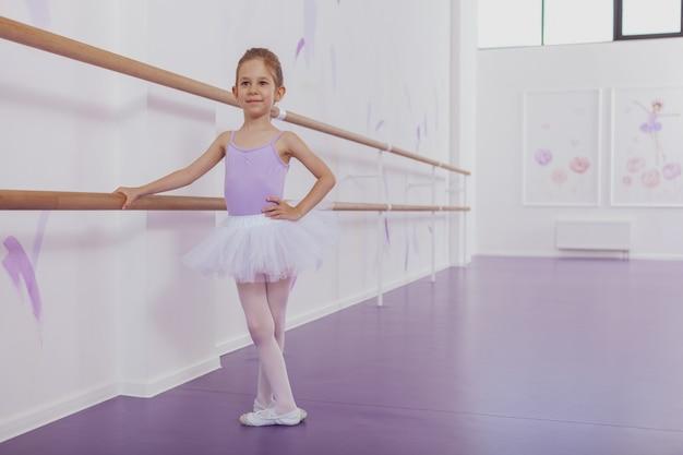 Disparo de cuerpo entero de una encantadora bailarina vestida con leotardo violeta y tutú bailando ballet en la clase de baile