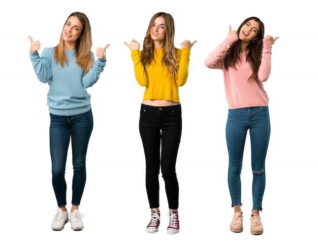 Un disparo de cuerpo entero de un grupo de personas con ropas coloridas dando un gesto con los pulgares arriba