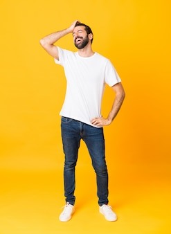 El disparo de cuerpo entero del hombre con barba sobre amarillo aislado se ha dado cuenta de algo y tiene la intención de la solución
