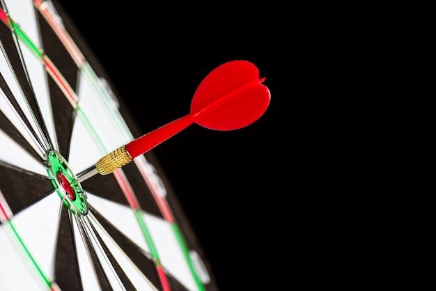 Disparó dardos rojos flechas en el centro de destino sobre fondo negro. concepto de objetivo de negocio.