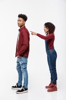 Disparo de estudio de dedo acusador de mujer enojada joven a su novio con expresión seria