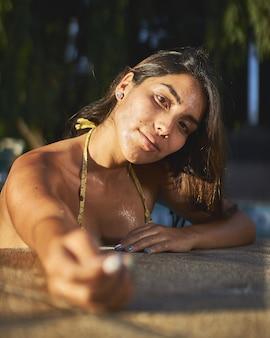 Disparo de enfoque selectivo de una atractiva mujer nativa americana posando en una piscina