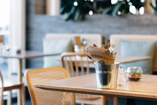 Disparo de enfoque selectivo de un cubo con tenedores y servilletas en una mesa de café de moda