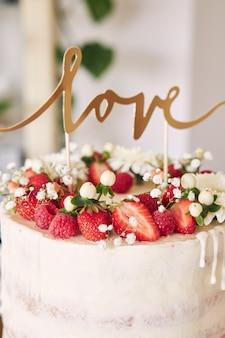 Disparo de enfoque selectivo de delicioso pastel de bodas blanco con frutos rojos, flores y adorno de torta