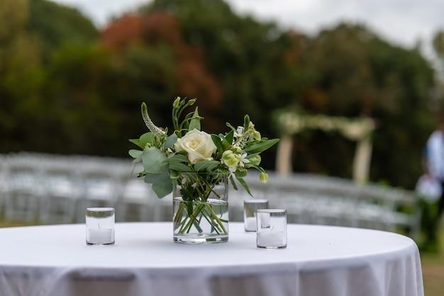 Disparo de enfoque selectivo de hermosas flores en un jarrón sobre una mesa en una ceremonia de boda