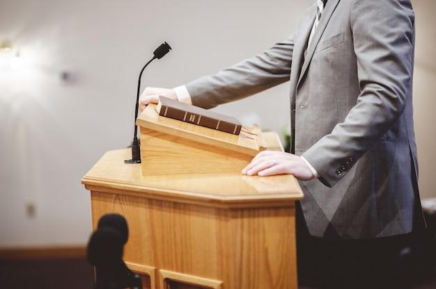 Disparo de enfoque selectivo de un hombre de pie y hablando desde el púlpito