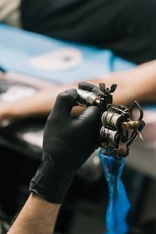 Disparo de enfoque selectivo de la mano de un tatuador con un guante negro y sosteniendo una pistola de tatuaje