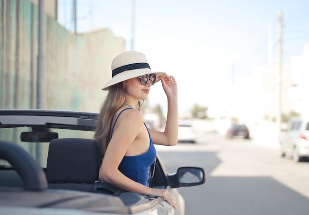 Disparo de enfoque selectivo de mujer en el asiento del conductor de un coche deportivo convertible blanco