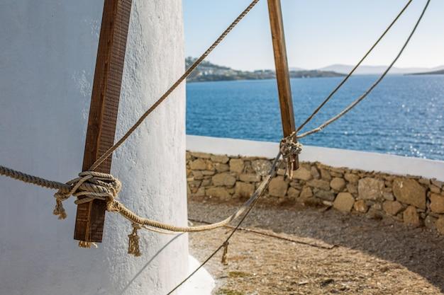 Disparo de enfoque selectivo de una parte inferior de una torre en el océano en mykonos, grecia