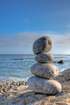 Disparo de enfoque selectivo de piedras apiladas en una orilla del mar con un cielo azul borroso