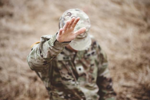 Disparo de enfoque selectivo de un soldado estadounidense con la mano levantada por encima