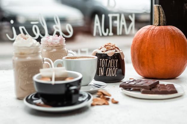 Disparo de enfoque selectivo de una variedad de bebidas calientes, barras de chocolate y una calabaza sobre la mesa