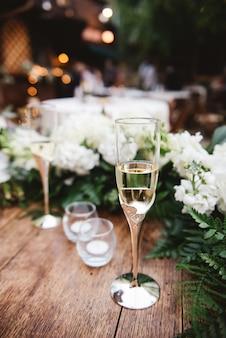 Disparo de enfoque selectivo vertical de una copa de champán sobre una superficie de madera en una boda