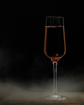 Disparo de enfoque selectivo vertical de una copa de champán sobre una superficie de madera y una distancia negra