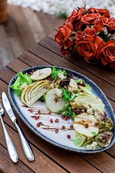 Disparo de enfoque selectivo vertical de ensalada de verduras en la mesa de madera Foto gratis