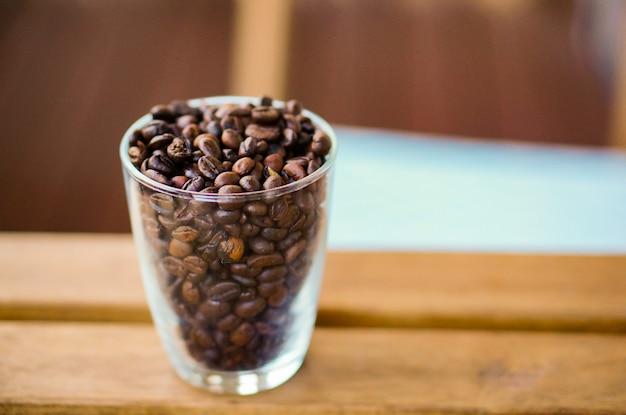 Disparo de enfoque selectivo vertical de granos de café en una taza transparente sobre una mesa de madera