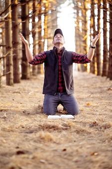 Disparo de enfoque selectivo vertical de un hombre rezando en un bosque