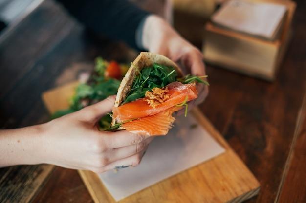 Disparo de enfoque suave del hombre que tiene un delicioso desayuno enorme en un restaurante o café fresco, pone guacamole o aguacate encima de una tostada de pan de centeno