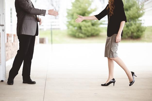 Disparo de enfoque superficial de un hombre y una mujer alcanzando el uno al otro para estrechar la mano por un edificio