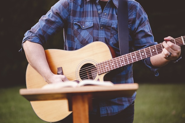 Disparo de enfoque superficial de un hombre tocando la guitarra cerca de un soporte de voz