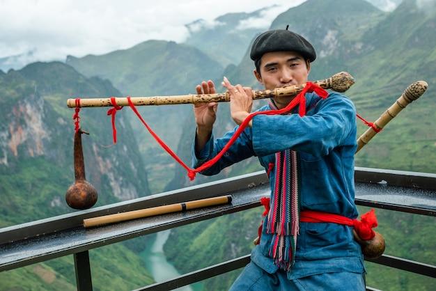 Disparo de enfoque superficial de un hombre vistiendo ropas tradicionales mientras toca un instrumento