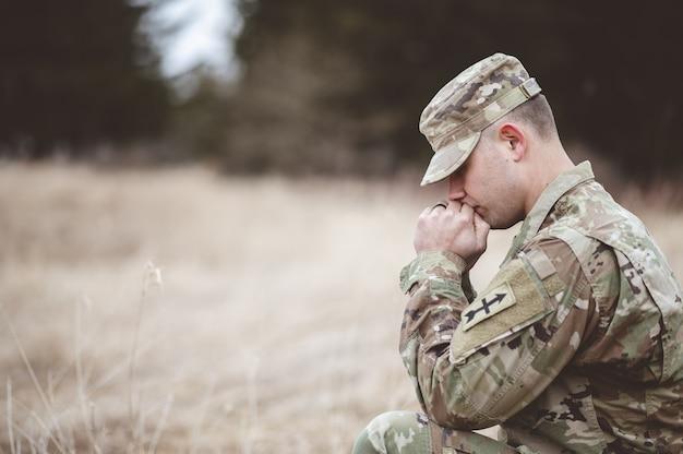 Disparo de enfoque superficial de un joven soldado rezando en un campo