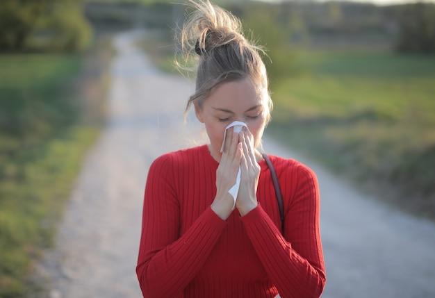 Disparo de enfoque superficial de una mujer vistiendo una blusa roja que está teniendo reacciones alérgicas estacionales