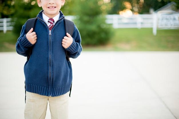Un disparo de enfoque superficial de un niño con su uniforme escolar