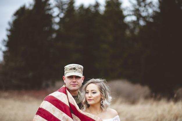 Disparo de enfoque superficial de un soldado estadounidense con su esposa envuelta en una bandera estadounidense