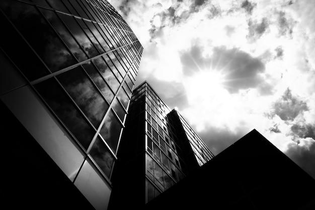 Disparo en escala de grises de ángulo bajo de edificios comerciales con un cielo nublado en el fondo