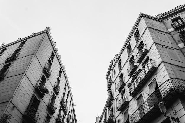Disparo en escala de grises de ángulo bajo de edificios residenciales uno frente al otro