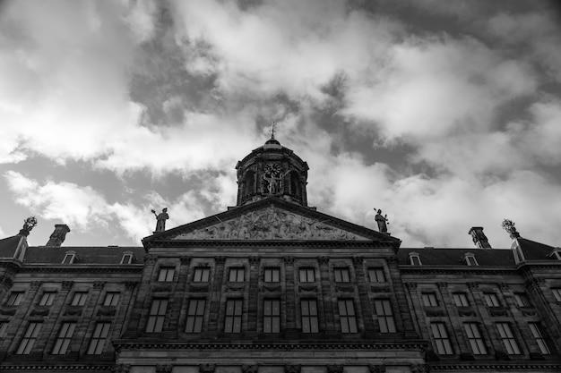 Disparo en escala de grises de ángulo bajo del palacio real en la plaza dam en ámsterdam, países bajos