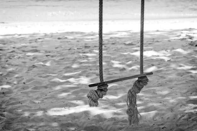 Disparo en escala de grises de un antiguo columpio de madera en la playa junto al mar