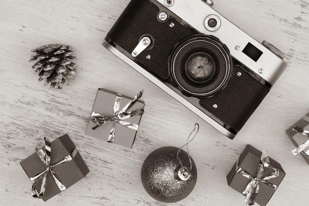 Disparo en escala de grises de la cámara y cajas de regalo de navidad