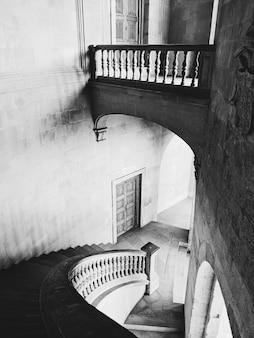Disparo en escala de grises de las escaleras y pasillos del palacio de la alhambra en granada, españa