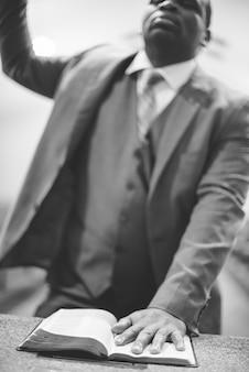 Disparo en escala de grises de un hombre afroamericano orando con su mano sobre la biblia