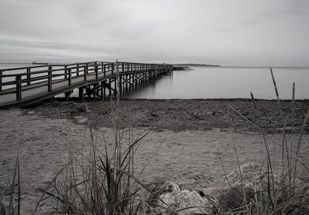 Disparo en escala de grises de un muelle en el mar rodeado por la playa bajo un cielo nublado