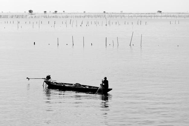 Disparo en escala de grises de una persona en una lancha en medio del mar en calma