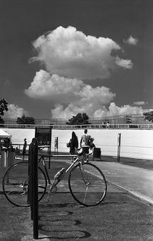 Disparo de escala de grises vertical de una bicicleta estacionada cerca de un estadio deportivo