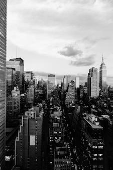 Disparo de escala de grises vertical de los edificios y rascacielos en la ciudad de nueva york, estados unidos