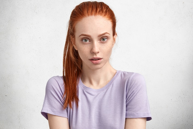 Disparo de estudio aislado de una hermosa joven con piel pecosa, cabello rojo, viste una camiseta púrpura casual, mira seriamente a la cámara, escucha al interlocutor con atención