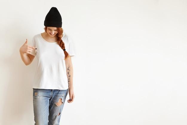 Disparo de estudio aislado de mujer joven con trenza mirando hacia abajo mientras ella apunta a su camiseta blanca en blanco