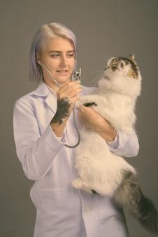 Disparo de estudio de médico joven y bella mujer con pelo corto de colores en gris
