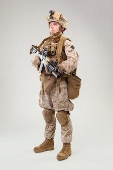 Disparo de estudio del soldado de infantería moderno, fusilero marino estadounidense con uniforme de combate, casco y armadura