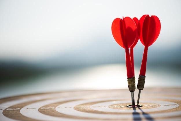Disparó flechas de dardos rojos en el centro de destino, objetivo o concepto de éxito objetivo.
