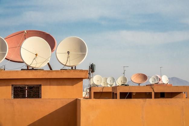 Disparo de gran angular de antenas parabólicas blancas en el techo de un edificio