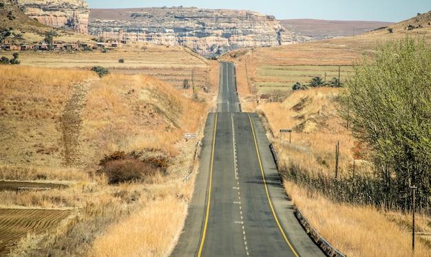 Disparo de gran angular de una carretera que va en una montaña rodeada de arbustos y pasto seco